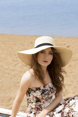 woman dress: romantic portrait of young woaman , sitting on the beach , wearing a summer hat and floral dress , sand on background Stock Photo