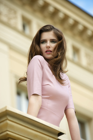 balcony: stunning brunette woman on balcony of old palace with long natural hair. stylish make-up and elegant pink dress looking beyond
