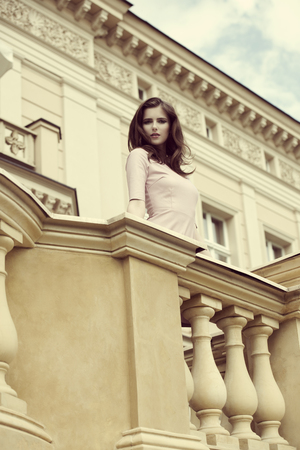 balcony: pretty elegant girl with pink dress posing on balcony of old building in outdoor fashion portrait