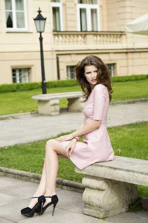 black heels: very beautiful young woman with elegant pink dress and black heels sitting on old bench in a  park with antique building on background Stock Photo