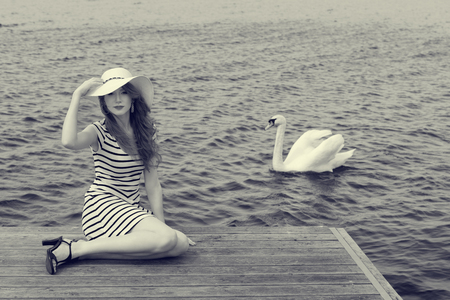 sea sexy: romantic shot of elegant woman in blue lined dress with hat she is sitting on the bridge near the lake with white swan coming.converted in black and white Stock Photo