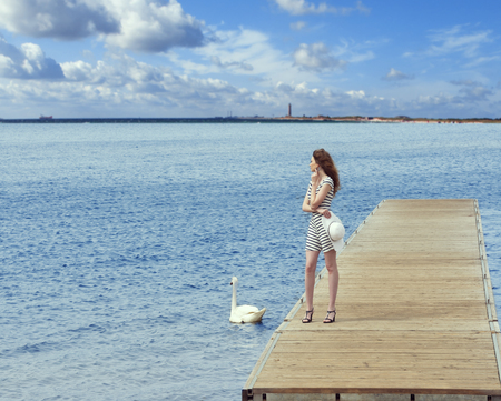 lady bird: romantic shot of a girl standing on wooden pier , in the lake with a white swan near her , summer day Stock Photo