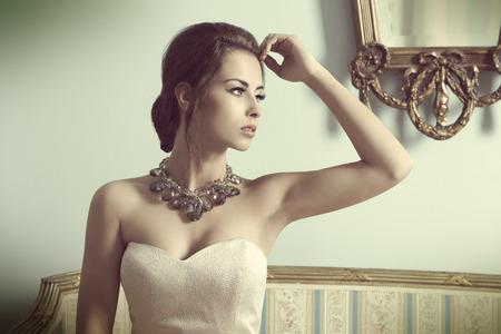 donne eleganti: bella donna bruna con stile aristocratico in posa sul divano antico in moda sparare al coperto con elegante abito rosa, brillante collana e elegante make-up.