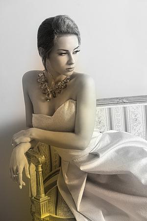 modelos negras: blanco y negro, encantadora morena elegante chica posando en la habitación de lujo en el sofá retro con un elegante vestido de color rosa, el cabello al estilo clásico y precioso collar brillante.