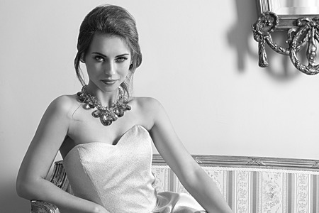 classic interior: black and white ,fashion indoor portrait of pretty brunette girl with aristocratic style sitting on ancient sofa with classic hair-style, wearing pink elegant dress and shiny necklace. Smiling and looking in camera