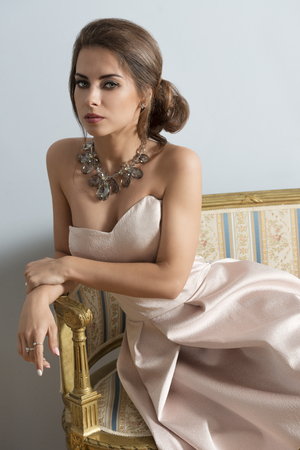old girl: elegant brunette girl with rich style posing with elegant pink dress and precious necklace on old sofa in indoor portrait