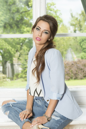 fashion shoot: indoor fashion shoot of cute brunette girl with casual trendy clothes, elegant hair-style and stylish make-up sitting near window on green garden. Wearing jacket and jeans