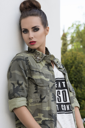 urban fashion: outdoor fashion portrait of beautiful brunette woman with modern urban style, creative make-up and strong stylish make-up.