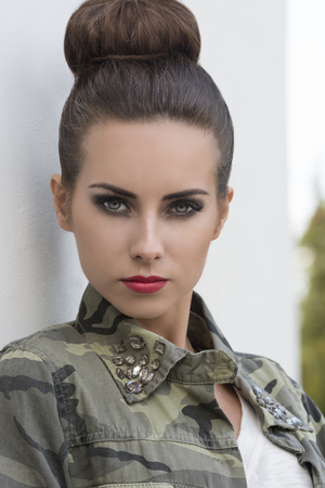 brunette girl: close-up outdoor portrait of pretty brunette girl with urban style and strong rock make-up. Wearing military shirt and creative hair-style Stock Photo