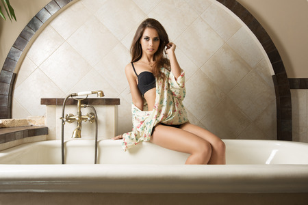 very sexy brunette model with black bikini and large floral shirt sitting in elegant retro rustic bathtub with long hair and sensual expression