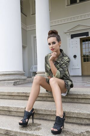 black heels: outdoor fashion shoot of charming brunette female with short dress, military shirt and black heels. Sitting on staircase of old building and looking in camera with dark stylish make-up