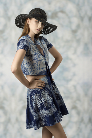 sexy female: charming female posing in fashion shoot with black hat and blue printed top and skirt. Looking in camera