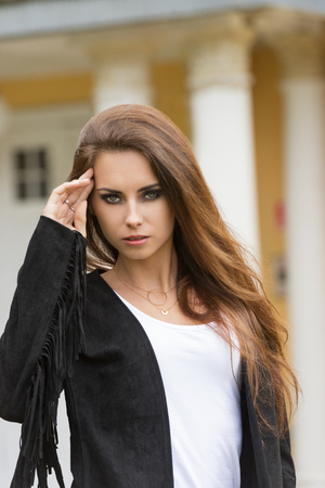 sensual girl: sensual young girl with long natural brown hair and stylish black make-up posing outdoor with old building on background looking in camera and wearing cute leather jacket Stock Photo
