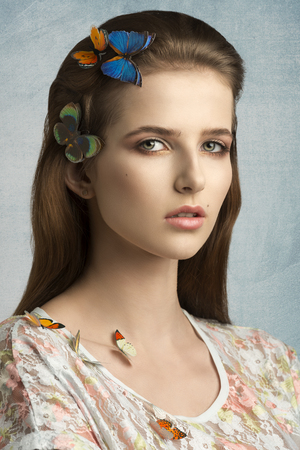 brunette girl: close-up beauty portrait of charming young girl with long brown hair and natural make-up posing with some colorful butterflies on head and shoulder