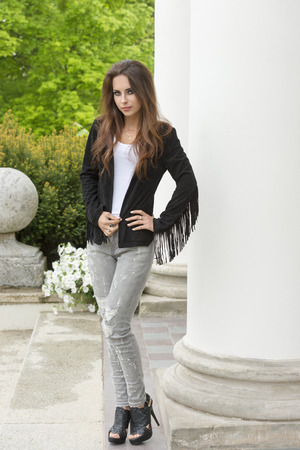 sexy female: very pretty brunette female with long natural hair and dark make-up posing outdoor near columns of old palace, wearing fringe dark leather jacket and urban torn jeans, sexy heels.