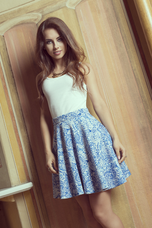 brunette girl: indoor shoot of very pretty brunette female posing near painted wall with long natural hair, stylish make-up, precious necklace and elegant blue skirt.