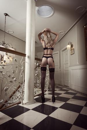 hermosa mujer rubia erótica mostrando su trasero sexy en ropa interior negro en pose sexy en lujo ambiente Foto de archivo