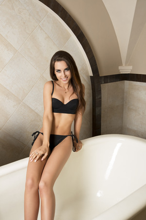 sensual girl: lovely brunette woman with bikini and fit body posing in elegant bathtub. Spa,  holydays and vacation concept