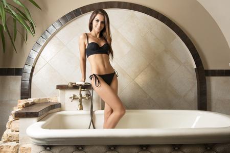 femme brune sexy: brunette fille sexy avec un corps parfait posant dans la baignoire dans l'élégant salle de bain rustique avec une expression détendue heureux Banque d'images