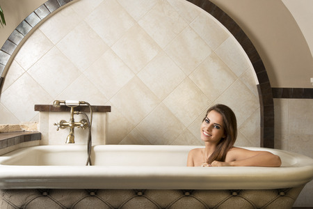 sexy bath: pretty brunette girl is sitting relaxed in a bathtub in elegant rustic bathroom in a luxury spa, smiling and looking in camera.