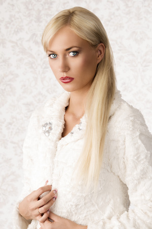 Winter fashion shoot of beautiful blonde girl with white fur coat, long cute hair and red lipstick. elegant rich style photo