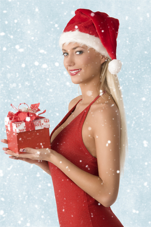 christmas portrait of lovely blonde woman with sexy dress and Santa Claus hat, she is smiling and taking gift box in the hand photo