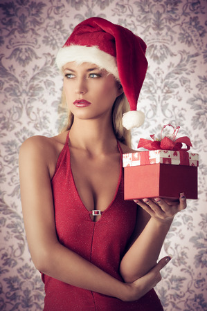 sexy girls party: sensual blonde female with sexy red dress and Santa Claus hat posing in christmas portrait with present in the hand