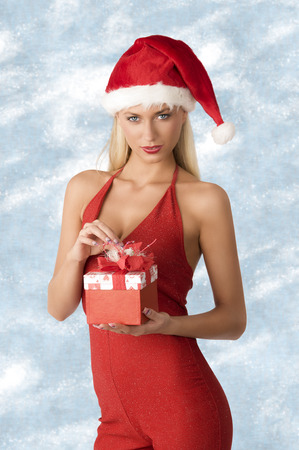 very pretty blonde woman with Santa Claus hat and sexy red dress posing with gift box in the hand and looking in camera with charming expression. Christmas concept photo