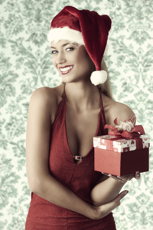 sexy blonde girl with christmas style taking gift box in the hand, smiling and looking in camera photo
