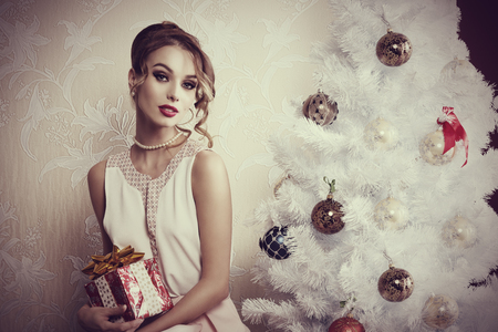 christmas present: indoor portrait of elegant woman with make-up and hair-style posing near decorated Christmas tree with gift box in the hand