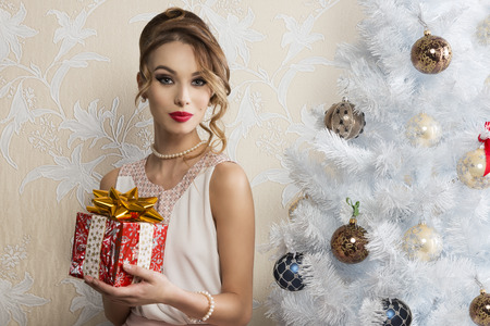 pearl: cute woman with elegant style and pearl necklace posing with make-up and hair-style near decorated christmas tree and taking gift box in the hand