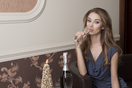 pretty dress: Christmas indoor shoot of sensual elegant woman drinking champagne in xmas night. Happy new year toast