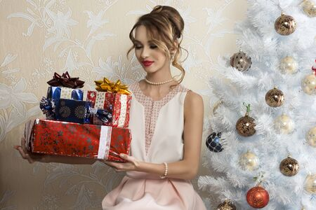 satisfy: elegant woman in interior xmas portrait sitting near decorated tree with some christmas presents in the hands and looking them with satisfy expression
