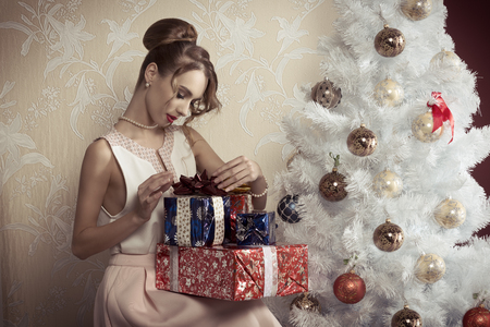 decorated christmas tree: elegant beautiful woman with hair-style sitting near decorated tree with some christmas presents. xmas concept.