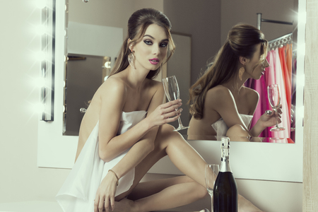 nude body: sensual girl sitting in bathroom near mirror with bottle of champagne and towel on her nude body. Preparing for new year party and drinking Stock Photo