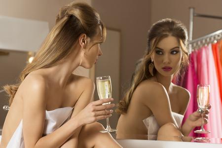 mujeres eroticas: muy sexy mujer se prepara para la fiesta de año nuevo y bebiendo champán. Mirando en el espejo en el baño y que cubre su cuerpo desnudo con una toalla Foto de archivo
