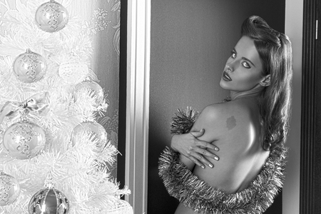 nude young: очаровательная брюнетка женщина позирует в XMas портрет рядом с декорированные деревом, повернулась на спину, прикрыв обнаженную грудь с светящейся мишуры в черно-белом