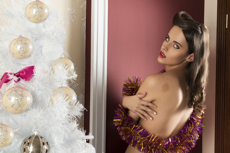 nude christmas: charming brunette woman posing in xmas portrait near decorated tree, turned on her back covering her nude breast with sparkly tinsel Stock Photo