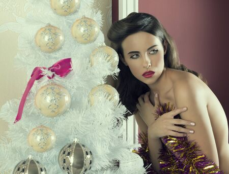 nude christmas: sexy brunette girl posing in christmas portrait with lovely make-up near decorated tree. covering her naked breast with sparkly tinsel