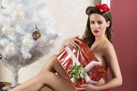naked woman sitting: beautiful brunette woman in sitting near christmas decorated tree and covering her naked breast with big gift box. wearing red ribbon at waistline