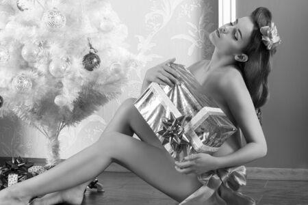 modelos desnudas: Mujer linda morena en pose erótica que se sienta cerca del árbol de navidad decorado y que cubre su pecho desnudo con caja de regalo. el uso de la cinta roja en la cintura Foto de archivo