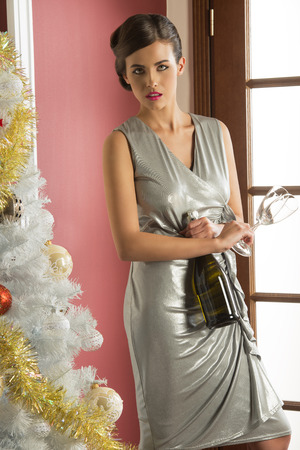 fashion dress: fashion elegant woman in christmas celebration near decorated tree taking a bottle of champagne in the hand and wearing elegant silver dress. xmas happy new year party Stock Photo