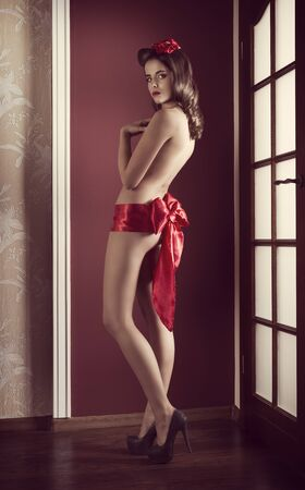 woman naked body: provocative brunette woman with fit naked body posing near decorated christmas tree and gift boxes, wearing only big red ribbon at waistline, heels and covering her nude breast Stock Photo