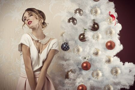 enraptured: sensual female with enraptured expression near decorated christmas tree. wearing elegant fashion  clothes, hair-style, cute make-up and precious pearl necklace Stock Photo
