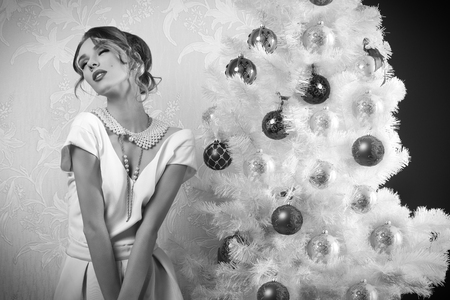enraptured: sensual female with enraptured expression near decorated christmas tree. wearing elegant fashion  clothes, hair-style, cute make-up and precious pearl necklace , in black and white shot
