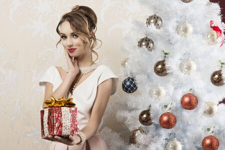 christmas woman: lovely fashion woman with elegant style, pearl necklace, stylish make-up and hair-style posing near christmas tree in indoor shoot with gift box in the hand