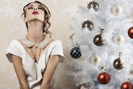 navidad elegante: muy elegante mujer bonita con el peinado, el maquillaje y collar de perlas posando con expresión relajada cerca de navidad decorado árbol Foto de archivo