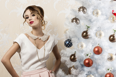 pearl: stunning woman with aristocratic elegant style near christmas decorated tree with hair-style, cute make-up and pearl necklace. xmas fashion holidays Stock Photo