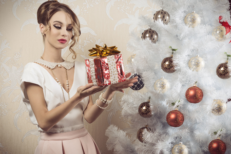 pearl: beautiful brunette woman with elegant fashion outfit, pearl necklace, hair-style and cute make-up taking christmas present in the hand near decorated xmas tree