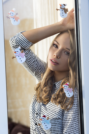 looking through window: pretty woman with freckles, natural make-up long hair and shirt in warm home looking  through window decorated with funny christmas stickers